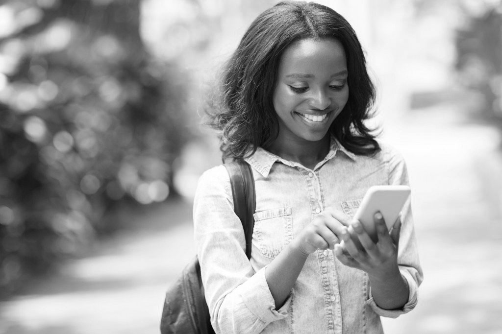 young african american uni student using cell phone