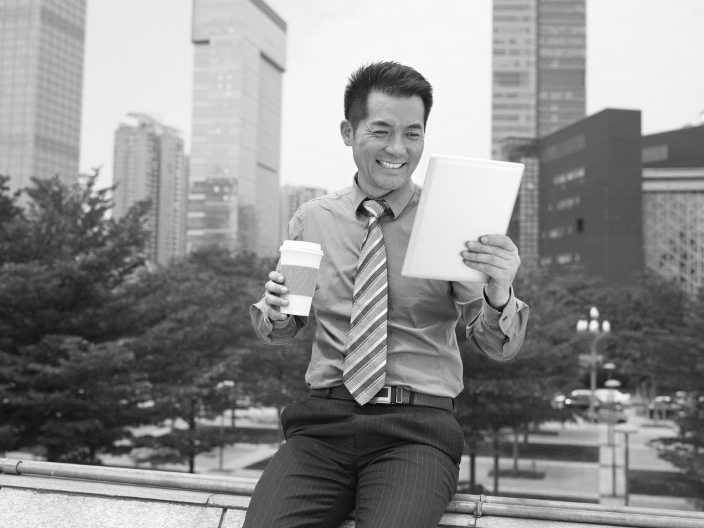 asian businessman looking at tablet holding coffee cup smiling.