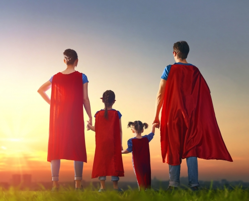Mommy, daddy and children girls in an Superhero's costumes. Concept of super family.