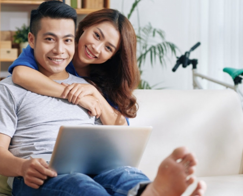 couple smiling in front of laptop