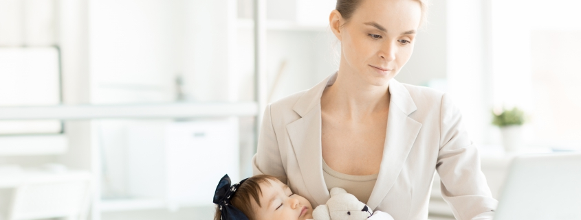 Cute baby with teddybear sleeping on arms of business mother browsing in the net by workplace